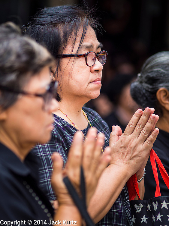 19 OCTOBER 2014 - BANG BUA THONG, NONTHABURI, THAILAND:  A woman prays at Apiwan Wiriyachai's cremation at Wat Bang Phai in Bang Bua Thong, a Bangkok suburb, Sunday. Apiwan was a prominent Red Shirt leader. He was member of the Pheu Thai Party of former Prime Minister Yingluck Shinawatra, and a member of the Thai parliament and served as Yingluck's Deputy Prime Minister. The military government that deposed the elected government in May, 2014, charged Apiwan with Lese Majeste for allegedly insulting the Thai Monarchy. Rather than face the charges, Apiwan fled Thailand to the Philippines. He died of a lung infection in the Philippines on Oct. 6. The military government gave his family permission to bring him back to Thailand for the funeral. His cremation was the largest Red Shirt gathering since the coup.    PHOTO BY JACK KURTZ