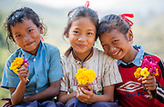 Three girls with flowers (Nepal)