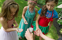 "Boys and Girls Club Dana Meade sprinkles special ""fairy dust"" into Kimmy, Elizabeth and Reese's hands as they decorate the fairy houses scattered among the gardens of Elaine Muller and Robert King prior to Opechee Garden Club's annual ""Awesome Blossoms"" Garden Tour Saturday.   (Karen Bobotas/for the Laconia Daily Sun)"