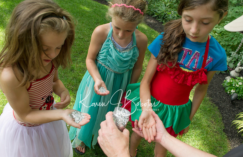 """Boys and Girls Club Dana Meade sprinkles special """"fairy dust"""" into Kimmy, Elizabeth and Reese's hands as they decorate the fairy houses scattered among the gardens of Elaine Muller and Robert King prior to Opechee Garden Club's annual """"Awesome Blossoms"""" Garden Tour Saturday.   (Karen Bobotas/for the Laconia Daily Sun)"""