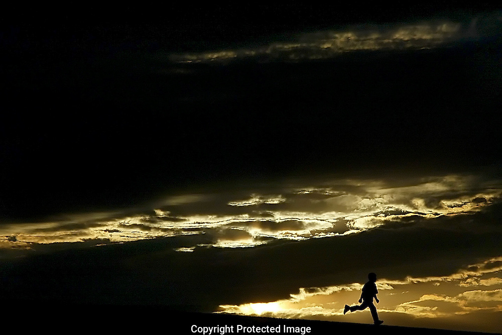 A child runs along the hill at Greyhound Stadium during an Eastern New Mexico University Football game.