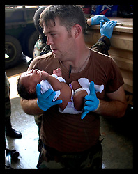 30th August, 2005. Triage at the Superdome in New Orleans. A soldier carries a baby into safety at the Superdome having been rescued from the flooded lower 9th ward by the Louisiana National Guard.