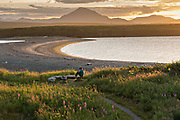 A camper watches the sunset over the Chigmit Mountains and McNeil Cove at the McNeil River State Game Sanctuary on the Kenai Peninsula, Alaska. The remote site is accessed only with a special permit and is the world's largest seasonal population of brown bears in their natural environment.