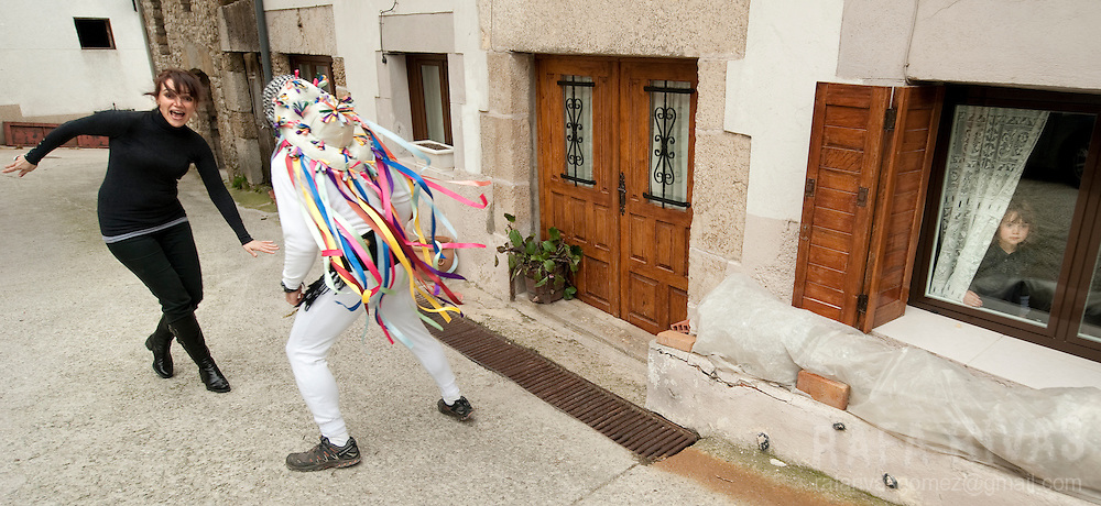 A momotxorro chases a woman during the ancient carnival of Unanu, North of Navarra province in Spain, on March 8, 2011. Momotxorros chase locals and slash them with sticks.   PHOTO/ RAFA RIVAS