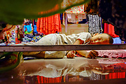 A small child is sleeping in his parents clothes shop at the fisherman village district, Koh Samui, Thailand