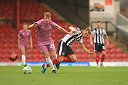 Andy Cannon is challenged by Jake Hessenthaler during the Carabao Cup match between Grimsby Town FC and Rochdale at Blundell Park, Grimsby, United Kingdom on 14 August 2018.