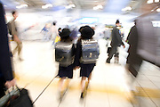 two little schoolchildren walking through a train station with large backpacks Tokyo Japan
