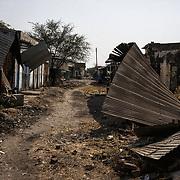 Une rue commerçante détruite, vestige des combats entre les rebelles et les SPLA (Armée Populaire de Libération du Soudan) à Malakal. La ville était la deuxième du pays avant la guerre civile en 2013. Véritable carrefour commercial, elle comptait plus de 150 000 habitants. Aujourd'hui, presque exclusivement des soldats loyalistes et leurs familles l'habitent.