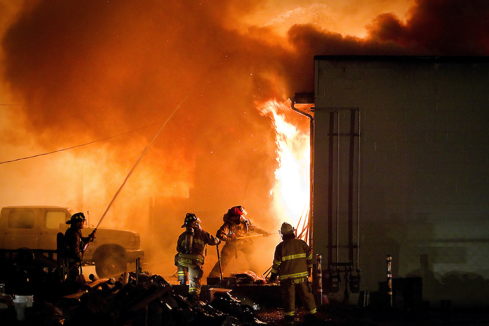Coeur d'Alene firefighters open a doorway to ventilate a fire that destroyed Performance RC Hobbies at 2928 Government Way in Coeur d'Alene Saturday night.