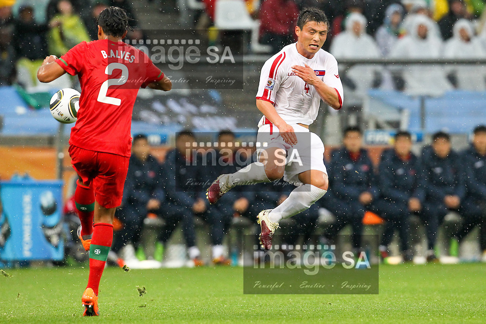 CAPE TOWN, SOUTH AFRICA, MONDAY 21 June 2010, PAK Nam Choi jumps before Bruno Alves kicks during the match between Portugal and Korea PRK held at the new Cape Town Stadium in Green Point during the 2010 FIFA World Cup..Photo by Roger Sedres/Image SA