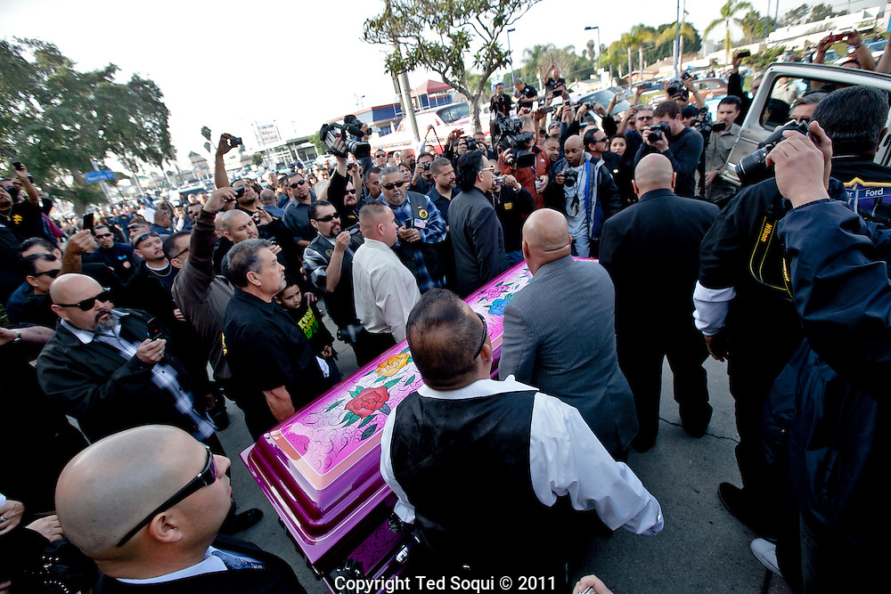 "Jesse Valadez's casket painted in the same style as his lowrider, Gypsy Rose."".Funeral procession for lowrider pioneer and founding member of the Imperials Car Club, Jesse Valadez..Valadez's  lowrider, ""Gypsy Rose"" a 1964 Chevy Impala with painted roses on each side and a bright pink interior, is considered to be the world's most famous lowrider by many car enthusiast. It was featured on the sitcom ""Chico and the Man,"" and took two and a half years to complete. .Hundreds of lowriders from the Imperial and fellow car clubs led a procession through East L.A., with the ""Gypsy Rose"" leading on a flat bed truck."