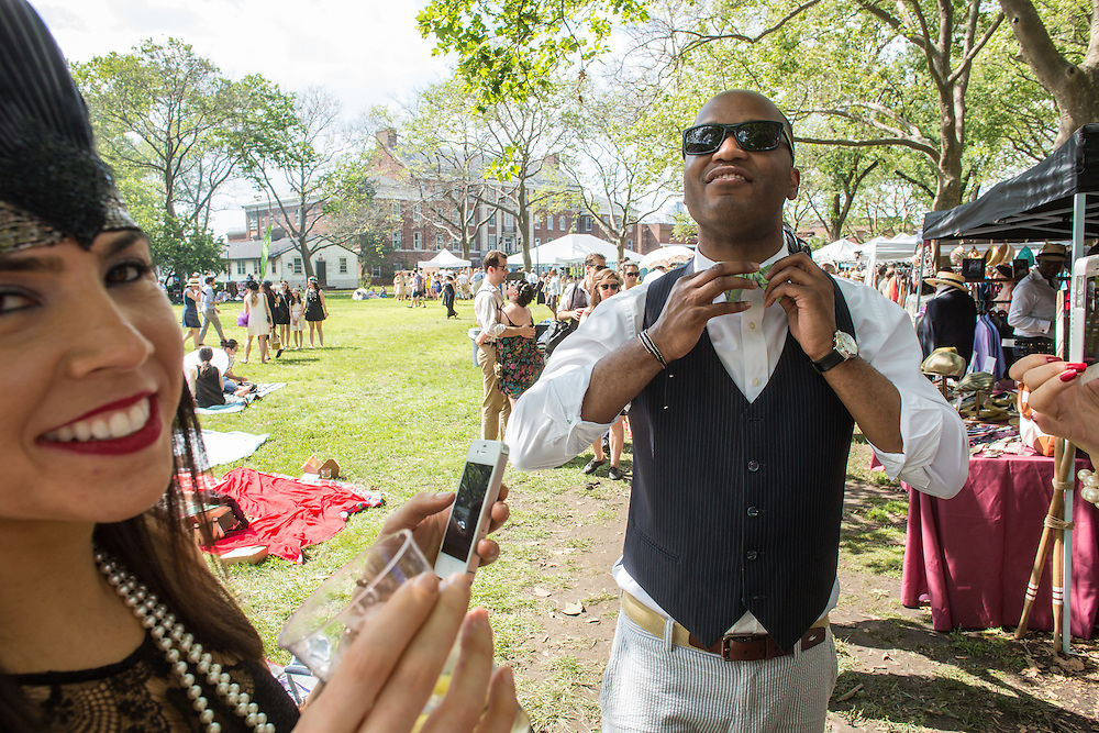 A man ties a newly-purchased bow tie at the Jazz Age Lawn Party. Vendors sold vintage clothing, and ties and hats were very popular.