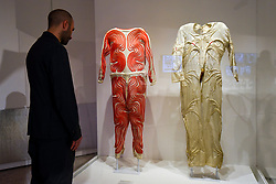 "© Licensed to London News Pictures. 17/10/2019. LONDON, UK. A staff member views (L to R) Liquid Cooled Altitude garment, 1977, and Air Cooled High Altitude garment, 1964. Preview of ""Moving to Mars"" at the Design Museum. The exhibition explores how sending humans to Mars is a frontier for science as well as design and features over 200 exhibits from NASA, the European Space Agency together with new commissions.  The show is open 18 October to 23 February 2020.  Photo credit: Stephen Chung/LNP"
