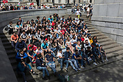 A group of foreign students sit on the steps in Trafalgar Square, on 9th May 2018, in London, England.