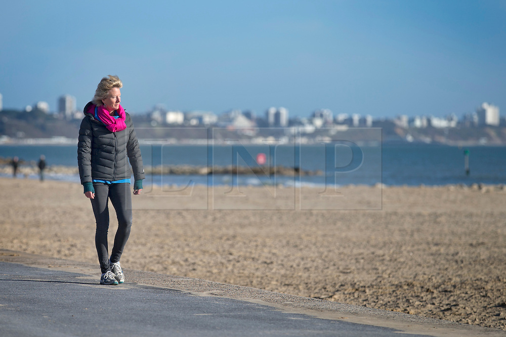 © Licensed to London News Pictures. 28/01/2016. Sandbanks, UK. A woman enjoys a stroll in the sunshine at Sandbanks in Dorset. Parts of the UK are enjoying a spell of sunshine after days of storms. Photo credit: Peter Macdiarmid/LNP