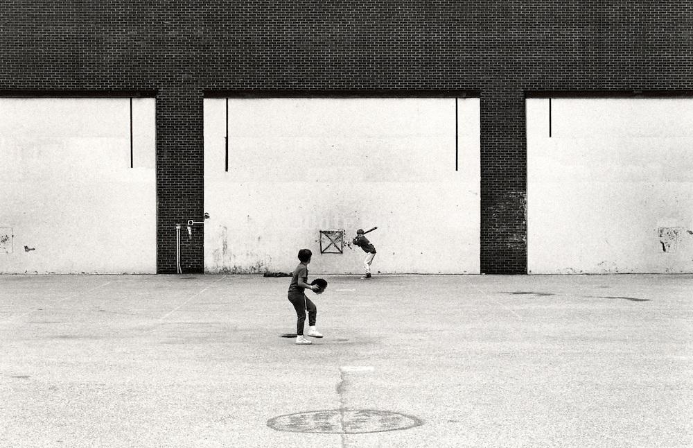 kids playing baseball in empty lot