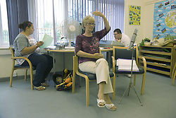 Day Service Officer using makaton a way of communicating with signs and symbols specially for people with learning difficulties whilst Care Assistant carries out paperwork in the background,