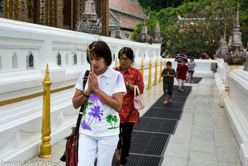 """22 JULY 2013 - PHRA PHUTTHABAT, THAILAND:  People pray and walk around the Mondop (chapel) at Wat Phra Phutthabat before the Tak Bat Dok Mai at Wat Phra Phutthabat in Saraburi province of Thailand, Monday, July 22. Wat Phra Phutthabat is famous for the way it marks the beginning of Vassa, the three-month annual retreat observed by Theravada monks and nuns. The temple is highly revered in Thailand because it houses a footstep of the Buddha. On the first day of Vassa (or Buddhist Lent) people come to the temple to """"make merit"""" and present the monks there with dancing lady ginger flowers, which only bloom in the weeks leading up Vassa. They also present monks with candles and wash their feet. During Vassa, monks and nuns remain inside monasteries and temple grounds, devoting their time to intensive meditation and study. Laypeople support the monastic sangha by bringing food, candles and other offerings to temples. Laypeople also often observe Vassa by giving up something, such as smoking or eating meat. For this reason, westerners sometimes call Vassa the """"Buddhist Lent.""""    PHOTO BY JACK KURTZ"""