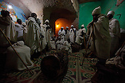 """Priests sing, pray and chant throughout the night during a special ceremony marking the birthday of the Saint of this ancient rock-hewn church. Occupying a high plateau and bordering with Eritrea in the very north of Ethiopia lies the ancient Province of Tigray. It is an area widely considered to be the fulcrum of Ethiopian culture with towns dated to before the birth of Christ. Distinctively different from the rest of Ethiopia, strongly Orthodox Christian and culturally proud, Tigray is a mountainous and rocky region dotted with ancient churches carved in to sandstone cliffs. Filling these churches are old religious manuscripts and Bibles safe-guarded by protective Priests. Its remoteness has protected the culture as well as the religious sanctuaries that have been described as """"the greatest of the historical-cultural heritages of the Ethiopian people"""". But now Tigray is at a crossroads. Improved infrastructure has led to an opening up of even the remotest towns and villages. Signs of modernity such as internet cafes and cell phones are increasingly being used by younger Tigraians dressed in jeans and T-shirts. Yet the Church remains an ancient and powerful institution which protects its ancient customs creating scenes that haven't changed since Biblical times.."""