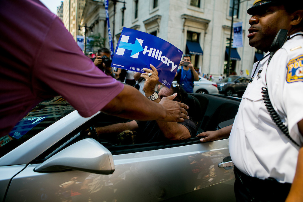 PHILADELPHIA, PA - JULY  25, 2016: A Hillary Clinton supporter waves a sign from his car as protesters demonstrate outside of Philadelphia City Hall in support of Democratic presidential candidate Bernie Sanders in Philadelphia, Pennsylvania. CREDIT: Sam Hodgson for The New York Times. <br /> <br /> NYTDNC