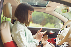 Profile of Teenage Girl Using Smartphone in Car