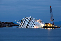 An oil recovery sea platform is seen next to the Costa Concordia cruise ship off the west coast of Italy, at dusk at Giglio island January 26, 2012. Italy's Civil Protection Agency expects to start extracting fuel from the capsized cruise ship by Saturday or earlier.<br /> REUTERS/Darrin Zammit Lupi (ITALY)