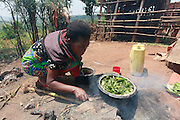 Marie Mukasharangabo - head of Mugorore village prepares lunch for her family using water she has collected from an offshoot of the Akagera river. Juru Sector. Bugesera district. Rwanda.<br /> <br /> Picture: WaterAid / Zute Lightfoot