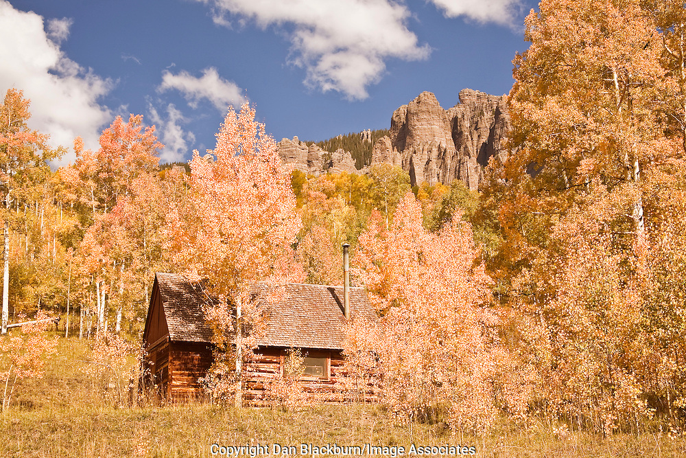 An old mountain cabin is surrounded by colorful Autumn aspens in the Cimarron Range in Colorado.
