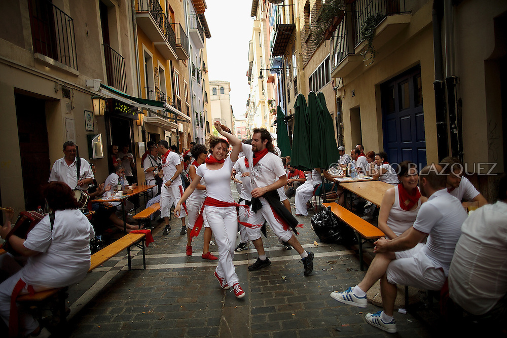 PAMPLONA, SPAIN - JULY 10: Revellers dance while musicians from Oberena play traditional Basque Country music in the street after having lunch on the fifth day of the San Fermin Running Of The Bulls festival on July 10, 2013 in Pamplona, Spain. The annual Fiesta de San Fermin, made famous by the 1926 novel of US writer Ernest Hemmingway 'The Sun Also Rises', involves the running of the bulls through the historic heart of Pamplona, this year for nine days from July 6-14.  (© Pablo Blazquez)