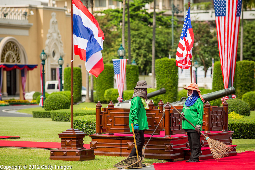 18 NOVEMBER 2012 - BANGKOK, THAILAND: Thai groundskeepers chat under fluttering Thai and US flags at Government House in Bangkok before President Obama's arrival in Thailand Sunday. US President Barack Obama arrives for the start of his tour of Southeast Asia on November 18, 2012 in Bangkok, Thailand. Barack Obama will become the first US President to visit Myanmar during the four-day tour of Southeast Asia that will also include visits to Thailand and Cambodia.   PHOTO BY JACK KURTZ