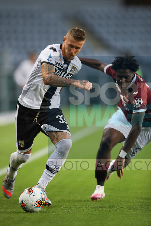 Parma Calcio's Slovak midfielder Juraj Kucka takes the ball past Torino FC's Nigerian defender Temitayo Ola Aina during the Serie A match at Stadio Grande Torino, Turin. Picture date: 20th June 2020. Picture credit should read: Jonathan Moscrop/Sportimage