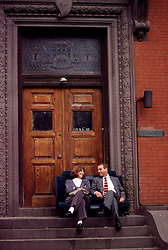 young couple sit on car seats at University of PA fraternity house steps