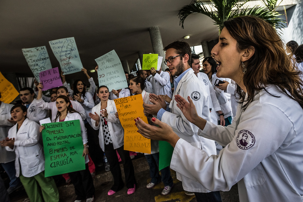 CARACAS, VENEZUELA - JANUARY 15, 2015: Doctors protest against their insecurity and the lack of medical supplies available for them to do their jobs, holding signs with details of their patients in need of care that they are unable to give them, because they lack the supplies necessary, infront of the state-run University City Hospital. Despite being a petro-state with one of the largest oil reserves in the world, basic and advanced medical supplies from gauze and surgical gloves, to heart stints, are difficult to find in hospitals and pharmacies across Venezuela.