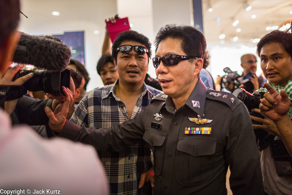 "01 JUNE 2014 - BANGKOK, THAILAND: A A Thai police officer looks for a man who protested against the coup in Terminal 21 shopping mall in Bangkok. The Thai army seized power in a coup that unseated a democratically elected government on May 22. Since then there have been sporadic protests against the coup. The protests Sunday were the largest in several days and seemed to be spontaneous ""flash mobs"" that appeared at shopping centers in Bangkok and then broke up when soldiers arrived. Protest against the coup is illegal and the junta has threatened to arrest anyone who protests the coup. There was a massive security operation in Bangkok Sunday that shut down several shopping areas to prevent the protests but protestors went to malls that had no military presence.    PHOTO BY JACK KURTZ"