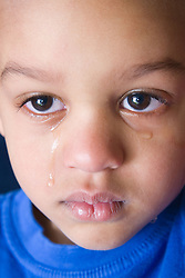 Upset young boy with tears streaming down his face,