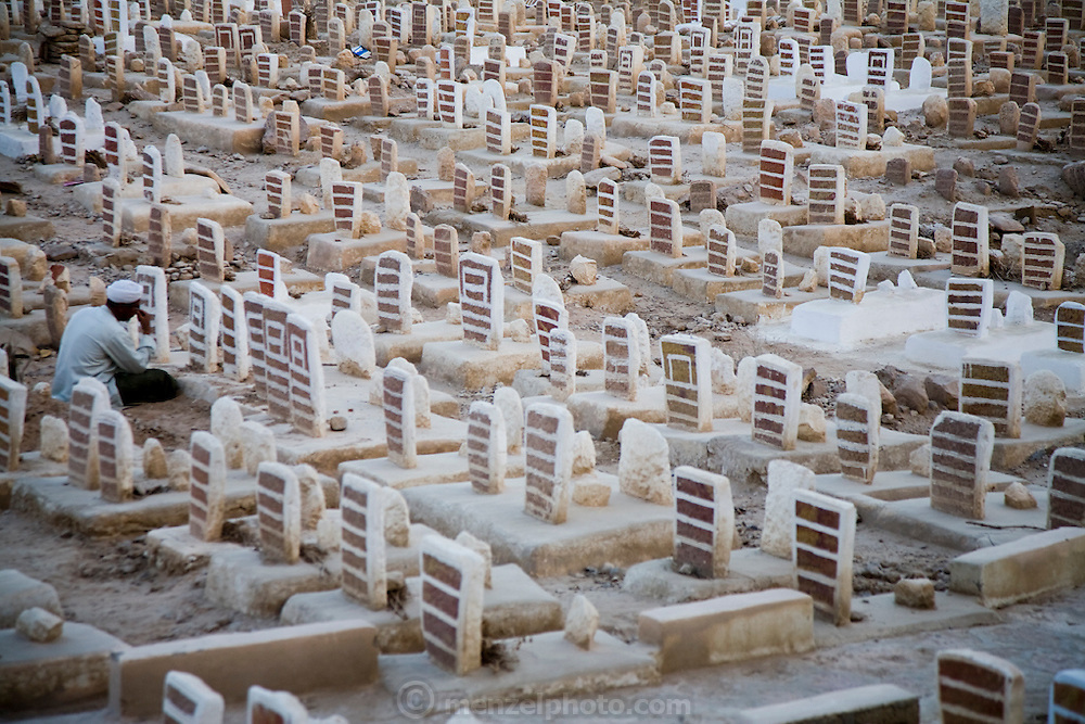 A man prays at a grave in the Muslim cemetery in the city of Tarim, Hadhramawt, Yemen.