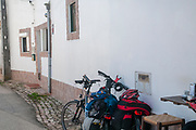 Bicycle tourists at rest at a small cafe in a Quaint blue and white houses line a street in a small town in the municipality of Obidos, Portugal