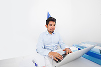 Businessman wearing party hat while using laptop in office