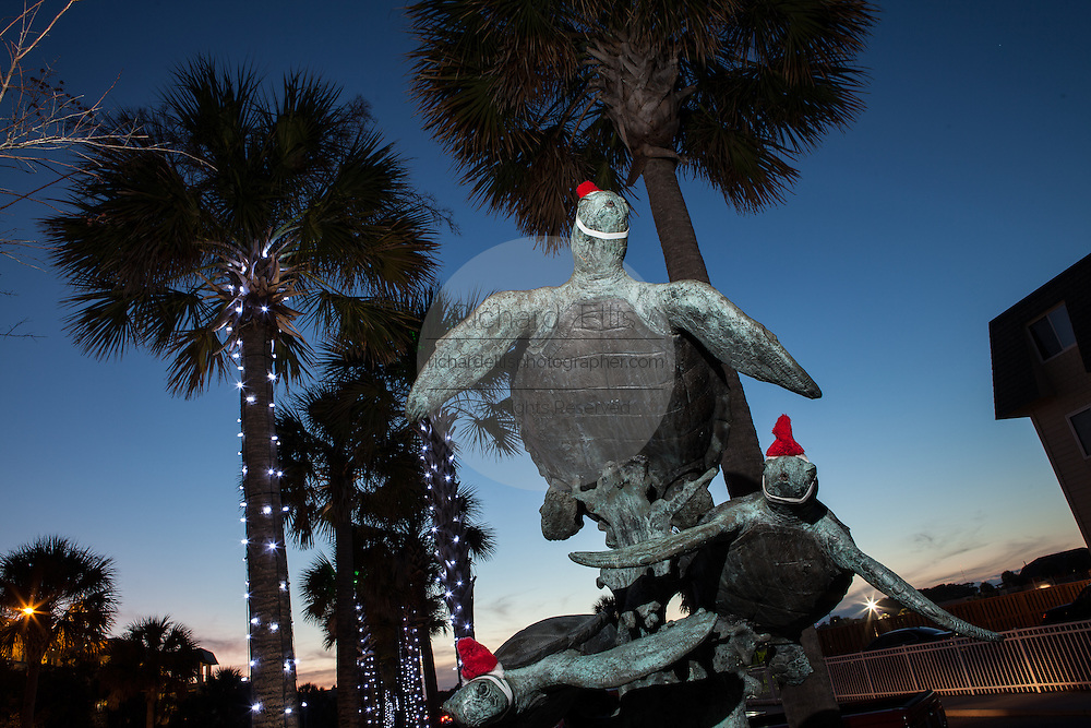 Loggerhead turtle statue decorated with santa hats on the Isle of Palms, SC.