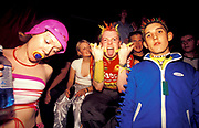A group of ravers wearing fluorescent clothing with dummy, glowsticks, glow-in-the-dark, spikey hair at a rave, U.K, 1990s.