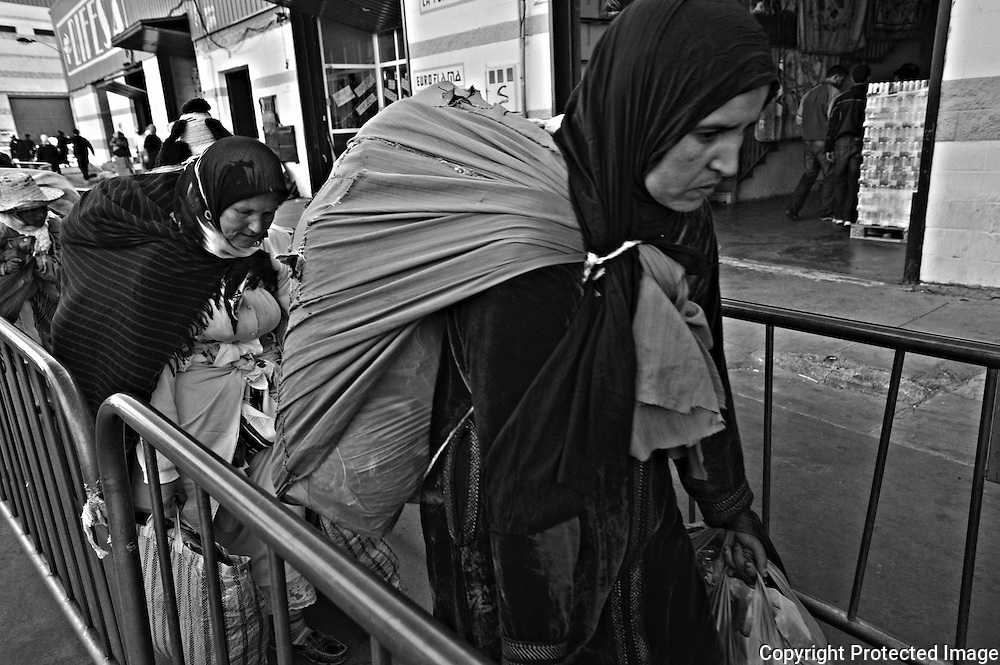 CEUTA, SPAIN - JUNE 27, 2010 : Moroccan women carrying goods on the passage of fences enabled in the warehouses next to the pedestrian cross border of El Biutz.. Thousands  of people are involved in transporting smuggled goods from Ceuta (an Spanish enclave on the North African coast) to Morocco, it is estimated that every day enter 10.000 porters, mostly women, that it make between three and five trips to Morocco with all types of products purchased on  the warehouse border area of El  Biutz in Ceuta, Spain.( Photo by Jordi Cami )
