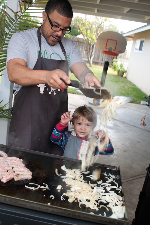 a look of fascination and excitement, on the face of a young boy as his father tosses onions to fry them on outside bbq