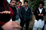 Local Afghani's of an area out of the main city Mytilene called Pamphila sit and debate over work and their future on the island of Lesvos.  Image © Angelos Giotopoulos/Falcon Photo Agency..