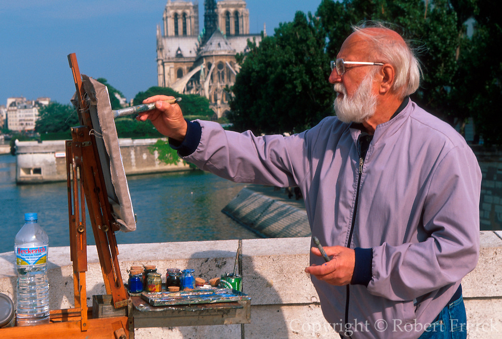 FRANCE, PARIS, CITY CENTER artist painting the view across the Seine to the Ile de la Cite and Notre Dame Cathedral