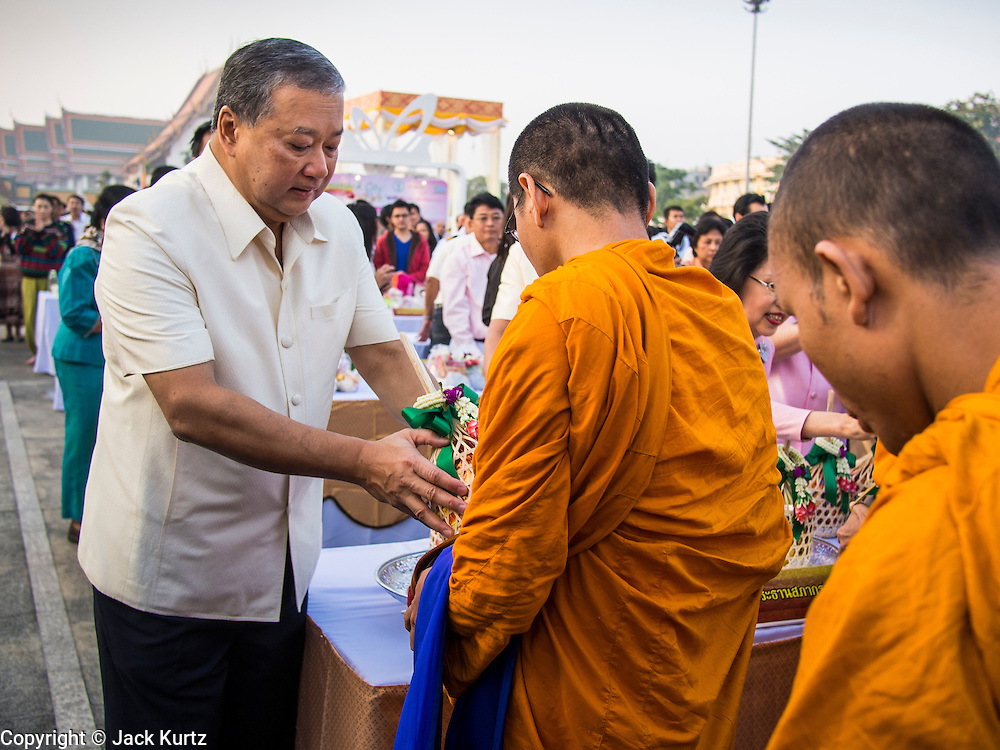 01 JANUARY 2014 - BANGKOK, THAILAND:  SUKHUMBHAND PARIPATRA, the Governor of Bangkok, presents offerings to Buddhist monks during the merit making ceremony at Bangkok City Hall. Several thousand people, mostly Bangkok city officials, gathered on the plaza of Bangkok City Hall Wednesday for the traditional New Year merit making ceremony.    PHOTO BY JACK KURTZ
