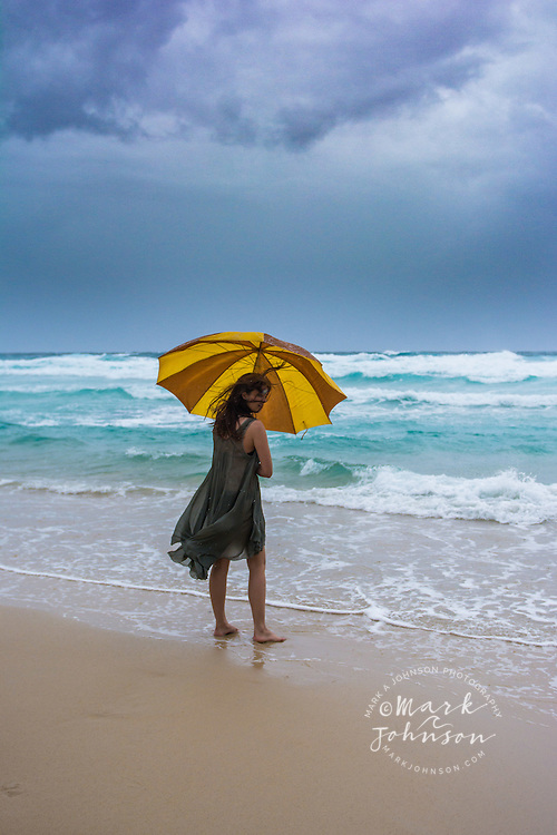 Young woman holding an umbrella on the beach on a stormy day, N. Stradbroke Island, Queensland, Australia people ****Model Release available