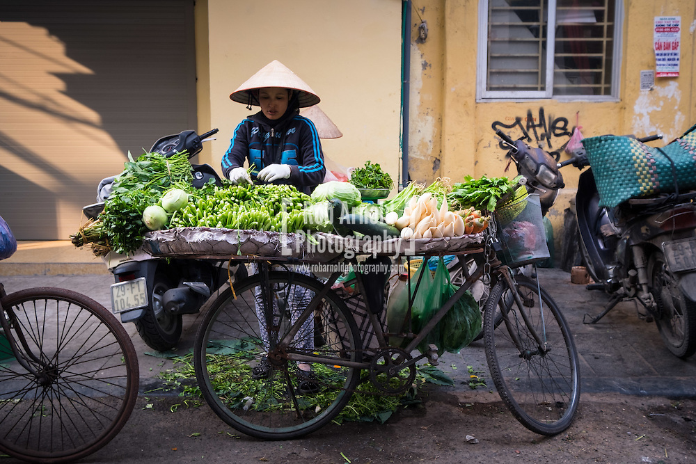 A street vendor selling vegetables from the back of her bicycle in Hanoi's Old Quarter