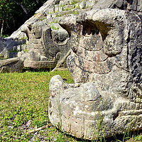 Snake Heads at The Ossuary at Chichen Itza, Mexico<br /> Snake head sculptures are such a common visual at Chichen Itza – like these at the base of The Ossuary's southern staircase – that they deserve more explanation. They represent Kukulkan, the Mayan snake god. He was known as the War Serpent (Waxaklahun Ubah Kan) during the Classic period (250 – 950 AD). Later he was referred to as the Vision Serpent and acted as a messenger between the ruler and the heavens. Belief of the deity began in Chichen Itza and then spread across Mesoamerica as a religious cult. Some experts believe the origin for the personified version of Kukulkan may represent a Chichen Itza ruler from the 10th century. According to folklore, Kukulkan was capable of flying across the earth and as high as the sun.