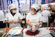 Chefs slice strawberries and crumble red velvet cake dough in the kitchen during the Grand Opening Ribbon Cutting Ceremony at Paris Baguette Cafe in Milpitas, California, on May 16, 2014. (Stan Olszewski/SOSKIphoto)