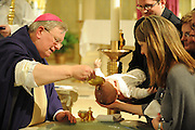 Bishop David Ricken baptizes an infant at Ss. Peter and Paul Church in Green Bay. (Sam Lucero photo)